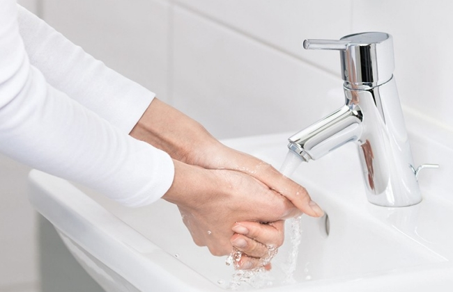 Healthcare professional cleans hands with soap and water.