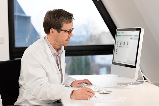 Trained personnel sitting at computer preparing medication with help of software.